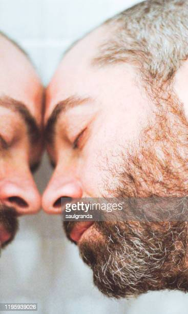 portrait of a bearded man with eyes closed leaning on a mirror - behaarte männer stock-fotos und bilder