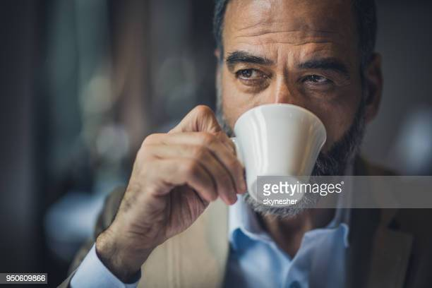 portrait of a bearded senior man drinking coffee in a cafe. - espresso stock photos and pictures