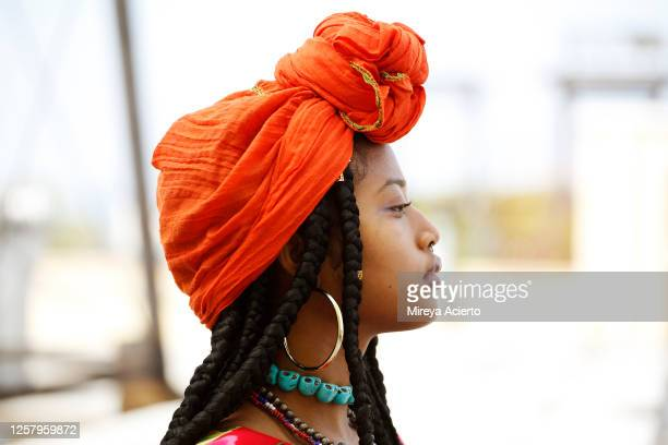 portrait of a beautiful african american woman wearing an orange head scarf, beaded necklaces and long dreads in an outdoor setting. - jewellery stock pictures, royalty-free photos & images