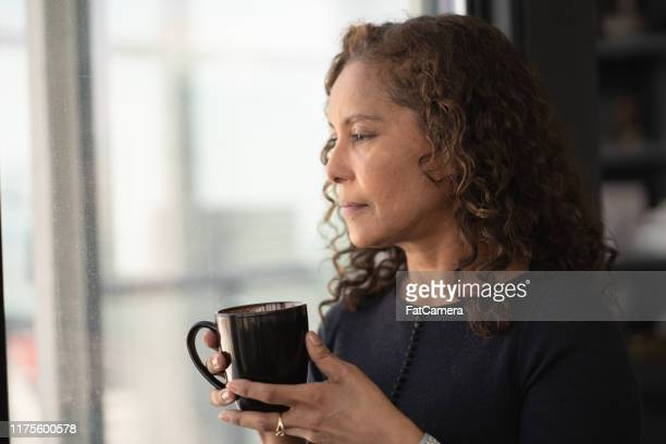 portrait of a beautiful black woman drinking tea by window - grief stock pictures, royalty-free photos & images