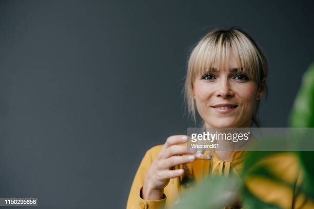 portrait of a beautiful blond woman, drinking iced tea - blonde glasses stock-fotos und bilder