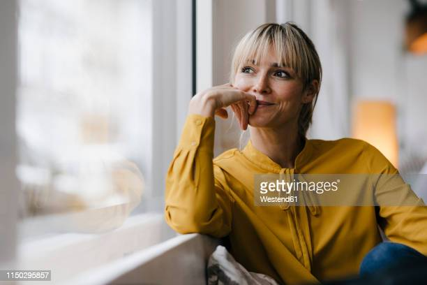 portrait of a beautiful blond woman, looking out of window - blouse stockfoto's en -beelden