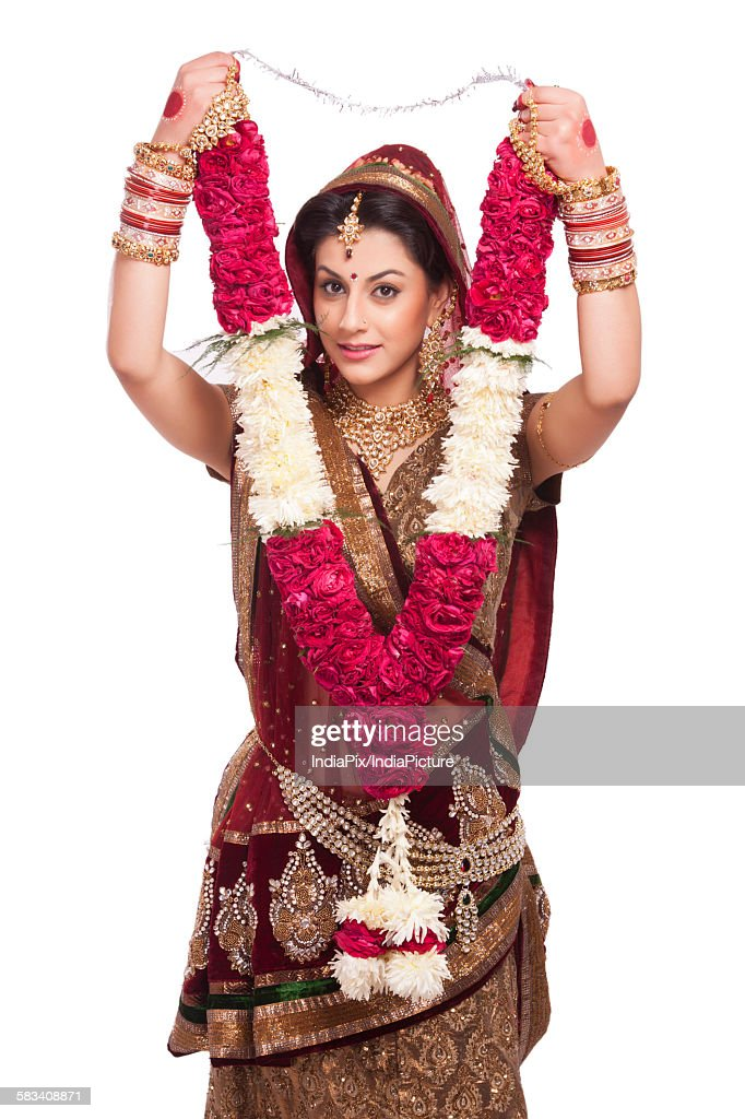 Portrait of a beautiful bride holding a garland : Stock Photo