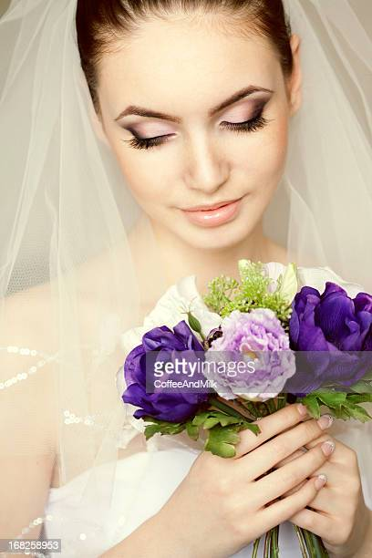 Portrait of a beautiful bride wearing veil with flowers