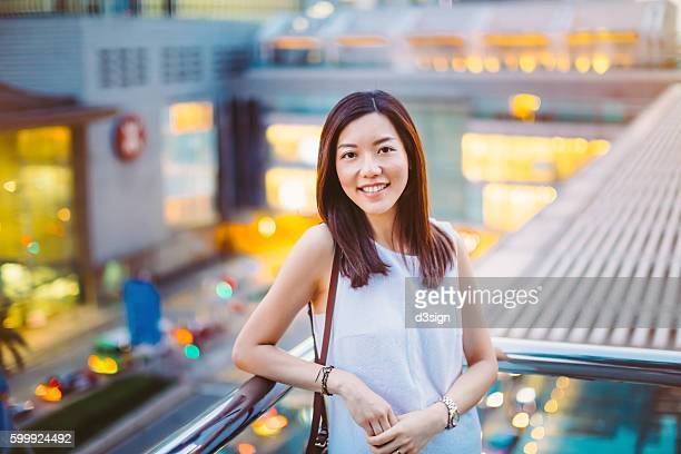 Portrait of a beautiful businesswoman leaning by the glass fence of roof terrace, with commercial buildings and busy city street behind as background.