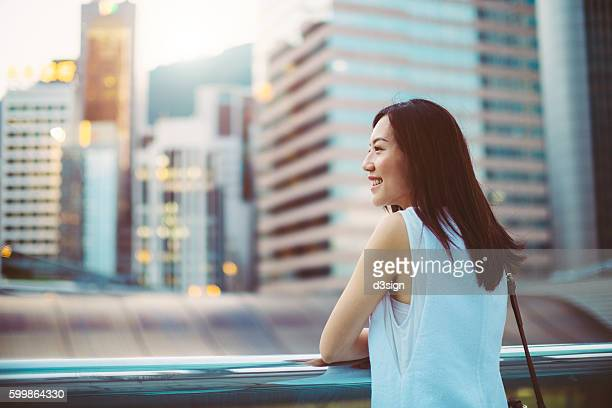 Portrait of a beautiful businesswoman leaning by the glass fence over the roof terrace, overlooking the city skyline.