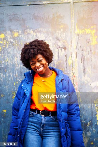 portrait of a beautiful fashionable young woman laughing on a painted backdrop - street style stock pictures, royalty-free photos & images