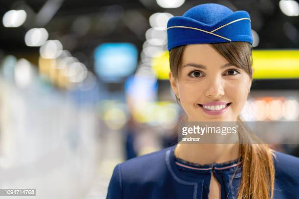 portrait of a beautiful flight attendant smiling at the airport - crew stock pictures, royalty-free photos & images