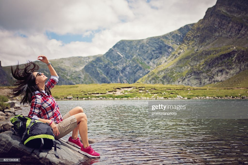 Portrait of a beautiful hiker girl sitting next to the high mountain lake : Stock Photo