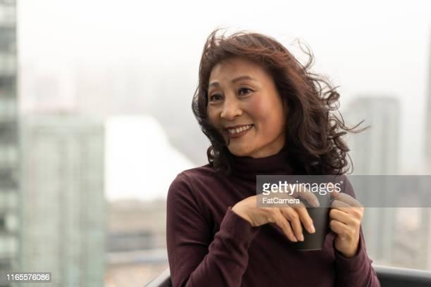 portret van een mooie koreaanse vrouw kijken naar de skyline van de stad - alleen één oudere vrouw stockfoto's en -beelden