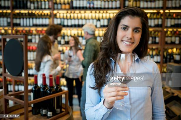 Portrait of a beautiful latin american woman at a winery looking at camera smiling while holding a wineglass with red wine