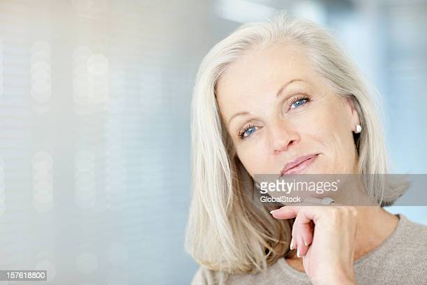 portrait of a beautiful mature woman with hand on chin - beautiful woman stockfoto's en -beelden