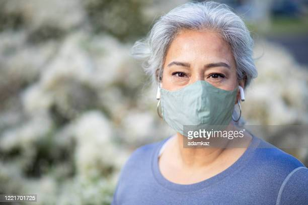 portrait of a beautiful mexican woman wearing a mask - adamkaz stock pictures, royalty-free photos & images