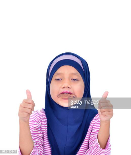 portrait of a beautiful muslim kid eat cookies isolated on white background - malaysia beautiful girl stock photos and pictures