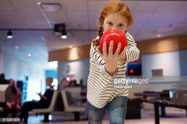 Portrait of a beautiful redhead girl playing Bowling