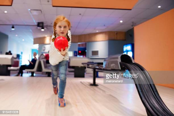 Portrait of a beautiful redhead girl playing Bowling