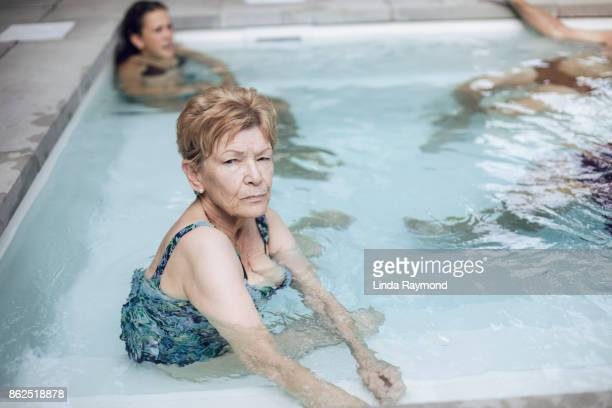 portrait of a beautiful senior woman in a hot tub - sun lounger stock pictures, royalty-free photos & images