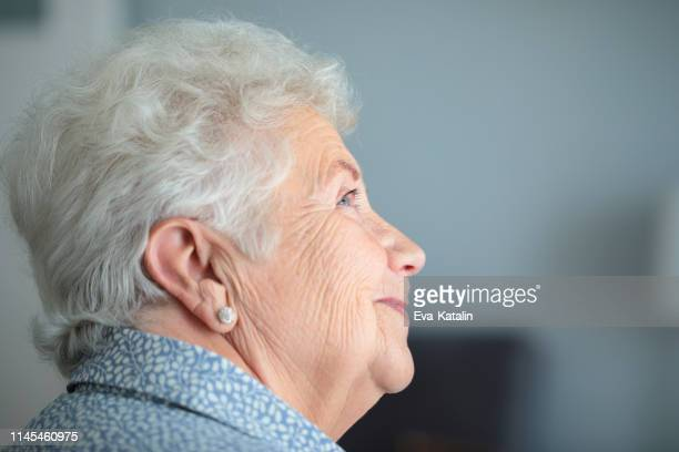 portrait of a beautiful senior woman - hearing aid stock pictures, royalty-free photos & images