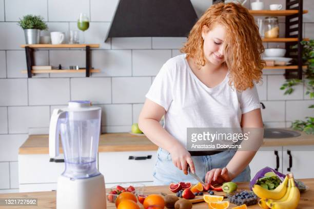 portrait of a beautiful smiling woman preparing smoothie at home kitchen. - fat nutrient stock pictures, royalty-free photos & images