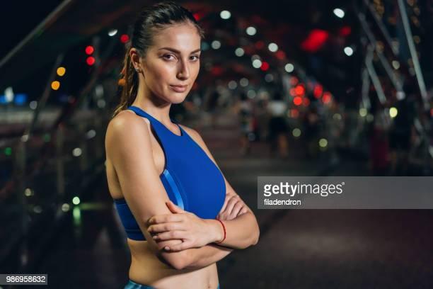 夜美しいスポーツウーマンの肖像画 - 陸上選手 ストックフォトと画像