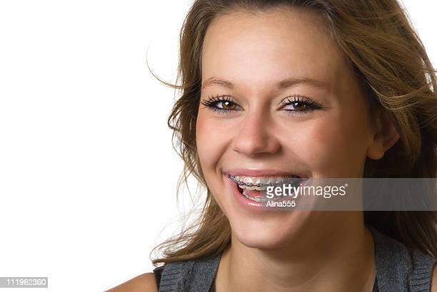 Ritratto di una bella adolescente con bretelle su bianco