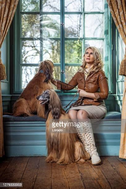 verticale d'une belle dame de pays de cru dans une maison majestueuse avec son crabot - une seule femme d'âge mûr photos et images de collection
