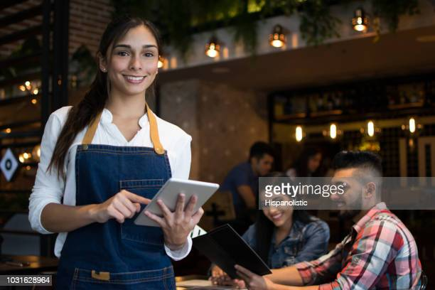 Portrait of a beautiful waitress at a bar holding a tablet computer