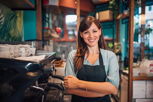 Portrait of a beautiful waitress wearing an apron, smiling at camera. 1168615808