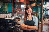 Portrait of a beautiful waitress wearing an apron, smiling at camera.