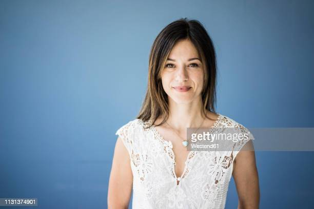 portrait of a beautiful woman against blue background - 40 44 years stock pictures, royalty-free photos & images