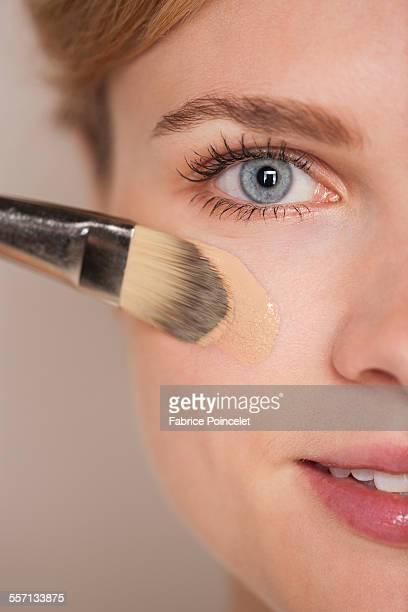 Portrait of a beautiful woman applying foundation
