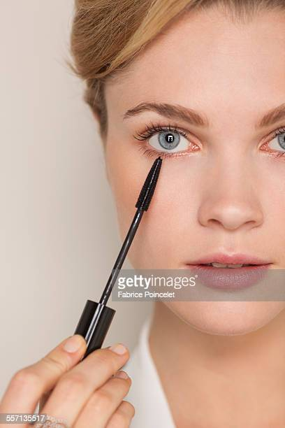Portrait of a beautiful woman applying mascara