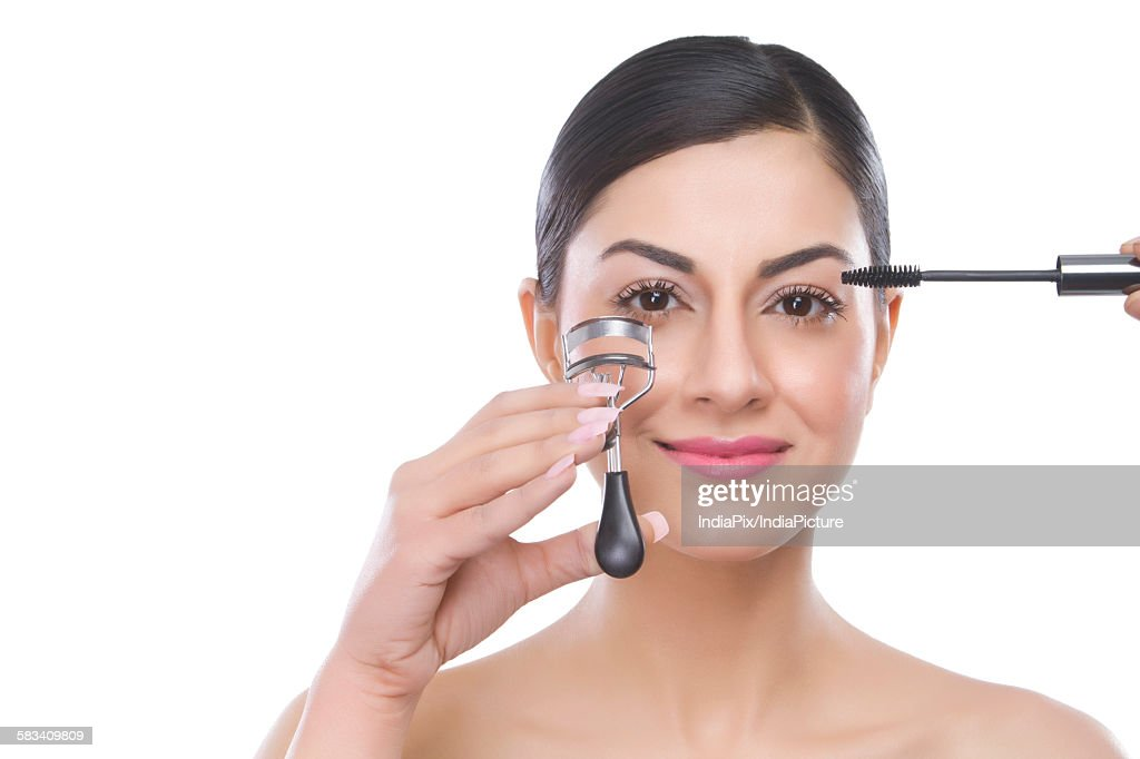 Portrait of a beautiful woman applying mascara : Stock Photo