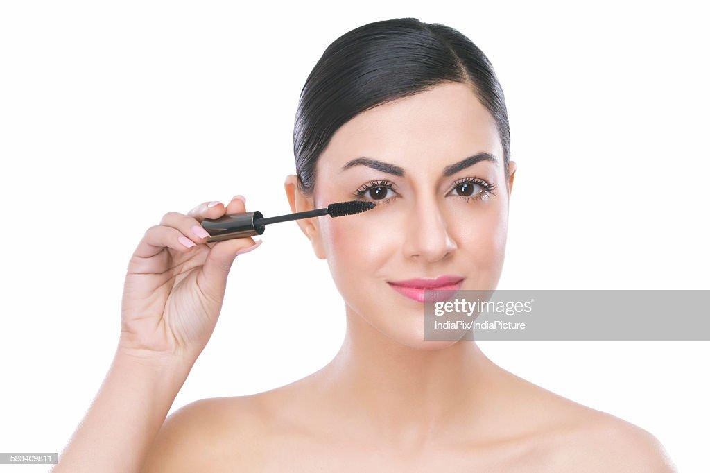 Portrait of a beautiful woman applying mascara : Stock Photo