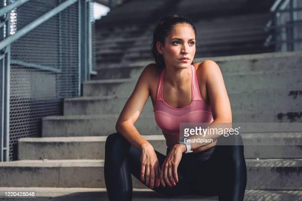 retrato de una mujer hermosa atleta en ropa deportiva sentado en las escaleras para descansar - sportsperson fotografías e imágenes de stock