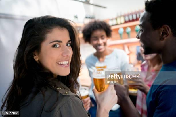Portrait d'une belle femme, boire de la bière avec ses amis en regardant la caméra en souriant