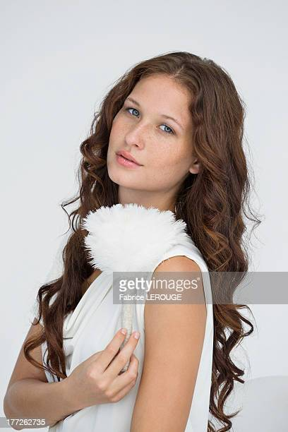 Portrait of a beautiful woman holding a feather duster