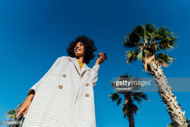 portrait of a beautiful woman, holding smartphone - low angle view stock pictures, royalty-free photos & images