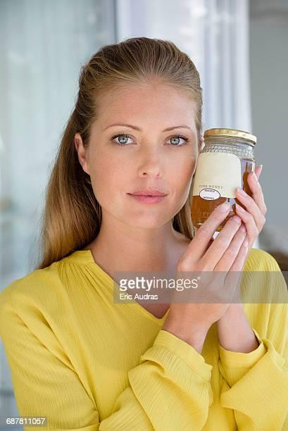 Portrait of a beautiful woman holing a jar of honey