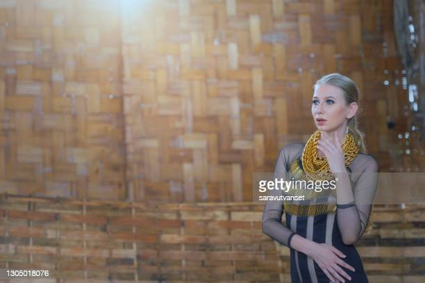 portrait of a beautiful woman in a long dress with her hand on her face, thailand - jewellery stock pictures, royalty-free photos & images