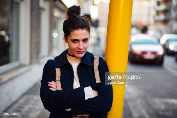 portrait of a beautiful woman leaning against a pole - topknot stock pictures, royalty-free photos & images