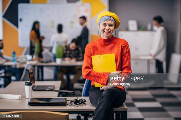 portrait of a beautiful woman sitting on desk in big modern office - blue hair stock pictures, royalty-free photos & images