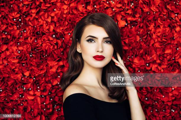 portrait of a beautiful woman standing against floral pattern - red lipstick stock pictures, royalty-free photos & images