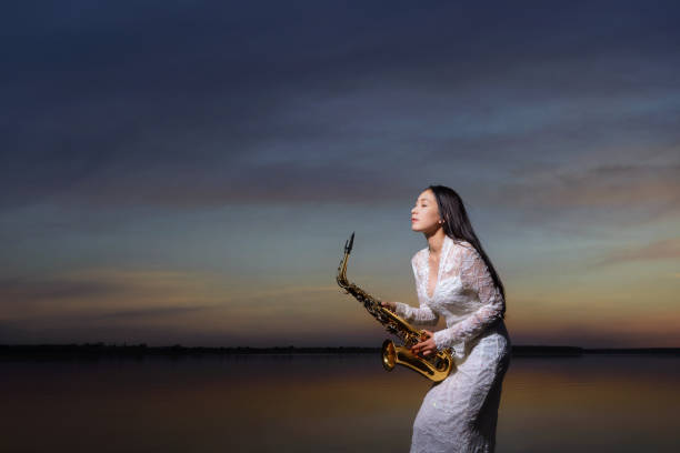 Portrait of a beautiful woman standing by a lake holding a saxophone