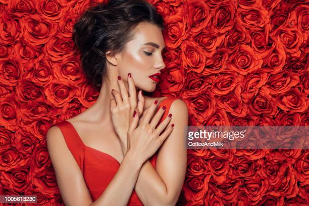 portrait of a beautiful woman standing in front of a floral pattern - rosaceae stock photos and pictures