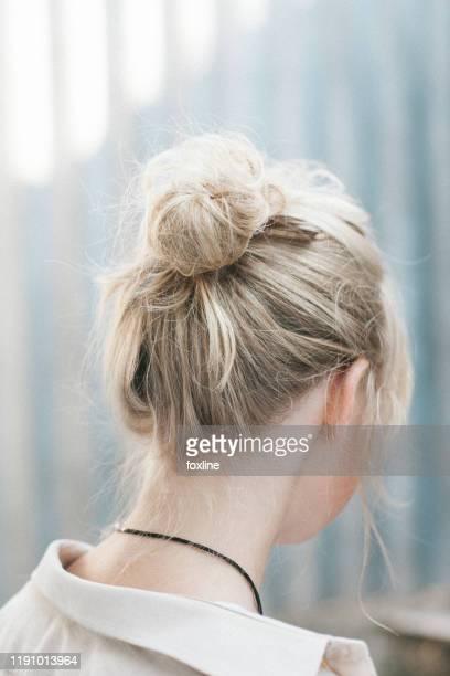 portrait of a beautiful woman with a hair bun - opgestoken haar stockfoto's en -beelden