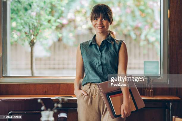 portrait of a beautiful young businesswoman holding her work essentials, about to start working at a bright cozy coffee house - sleeveless stock pictures, royalty-free photos & images