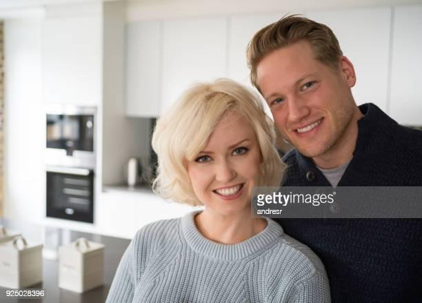 Portrait d'un standing beau jeune couple à la cuisine en regardant sourire caméra