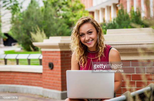 Portrait of a beautiful young female university student using her laptop outside on the campus