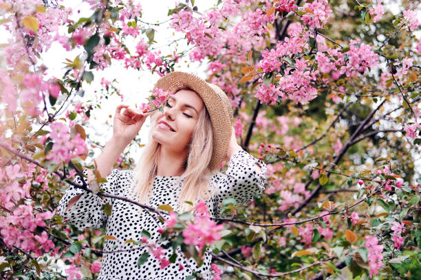 Portrait of a beautiful young girl in spring near a blooming pink apple tree